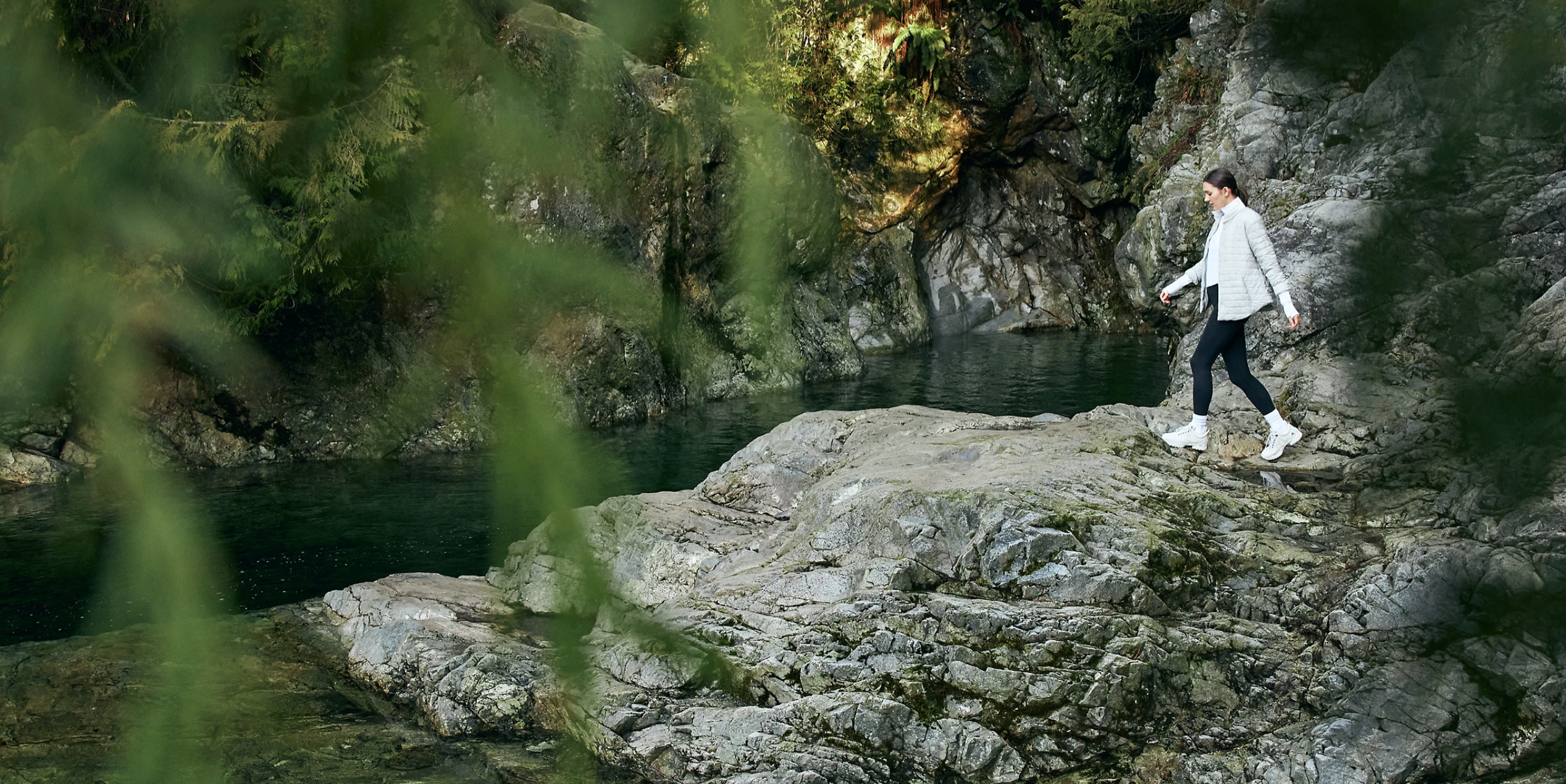 A woman hikes by a creek in a Lululemon ad.