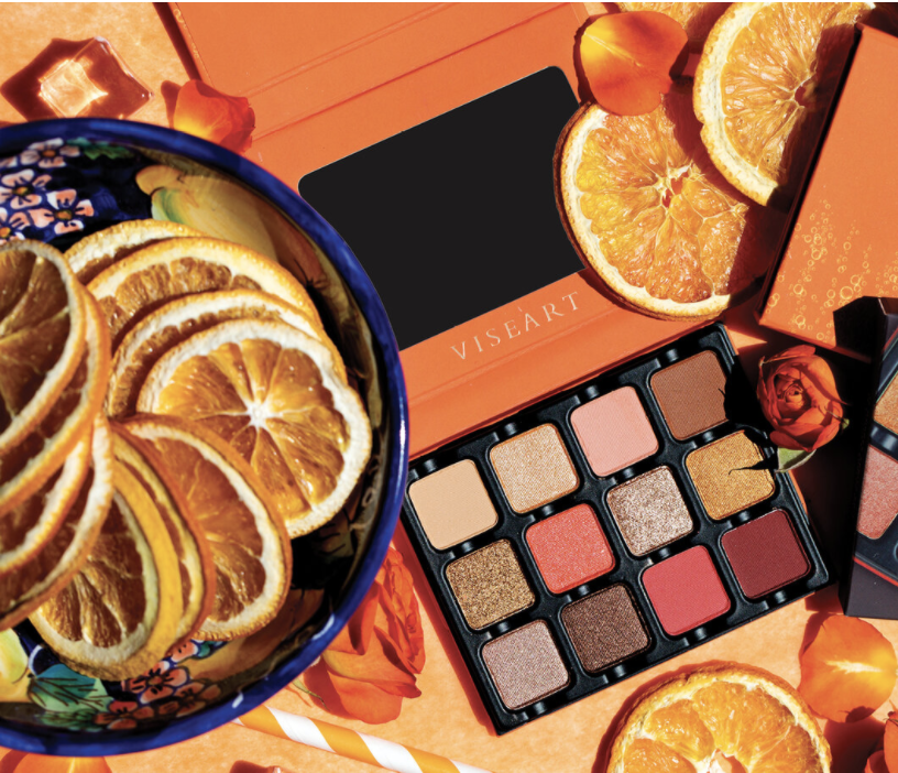 A photo featuring Viseart's Spritz Edit Eyeshadow Palette laying among orange slices and orange roses.