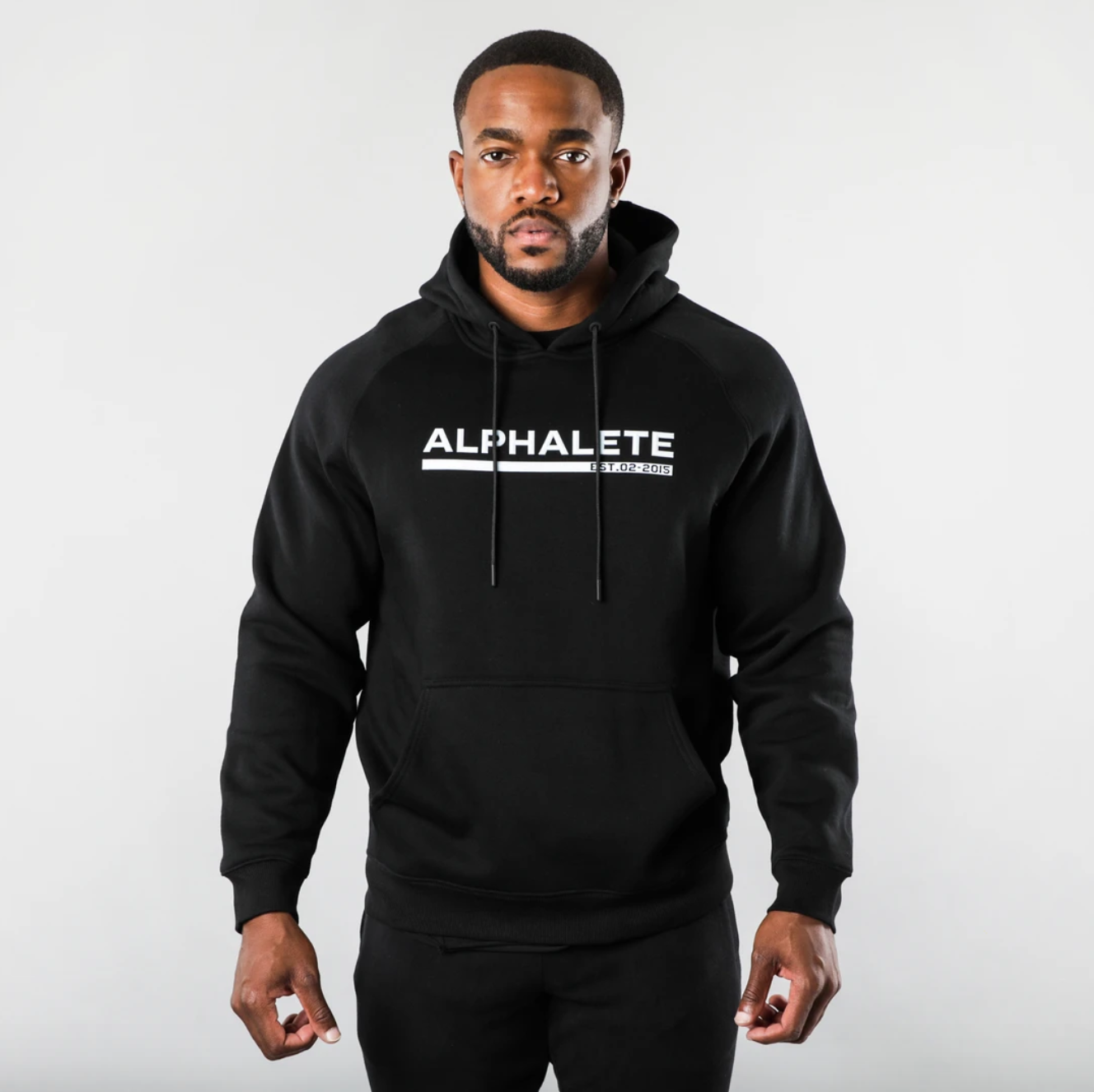 A male model poses in an Alphalete-branded hoodie.