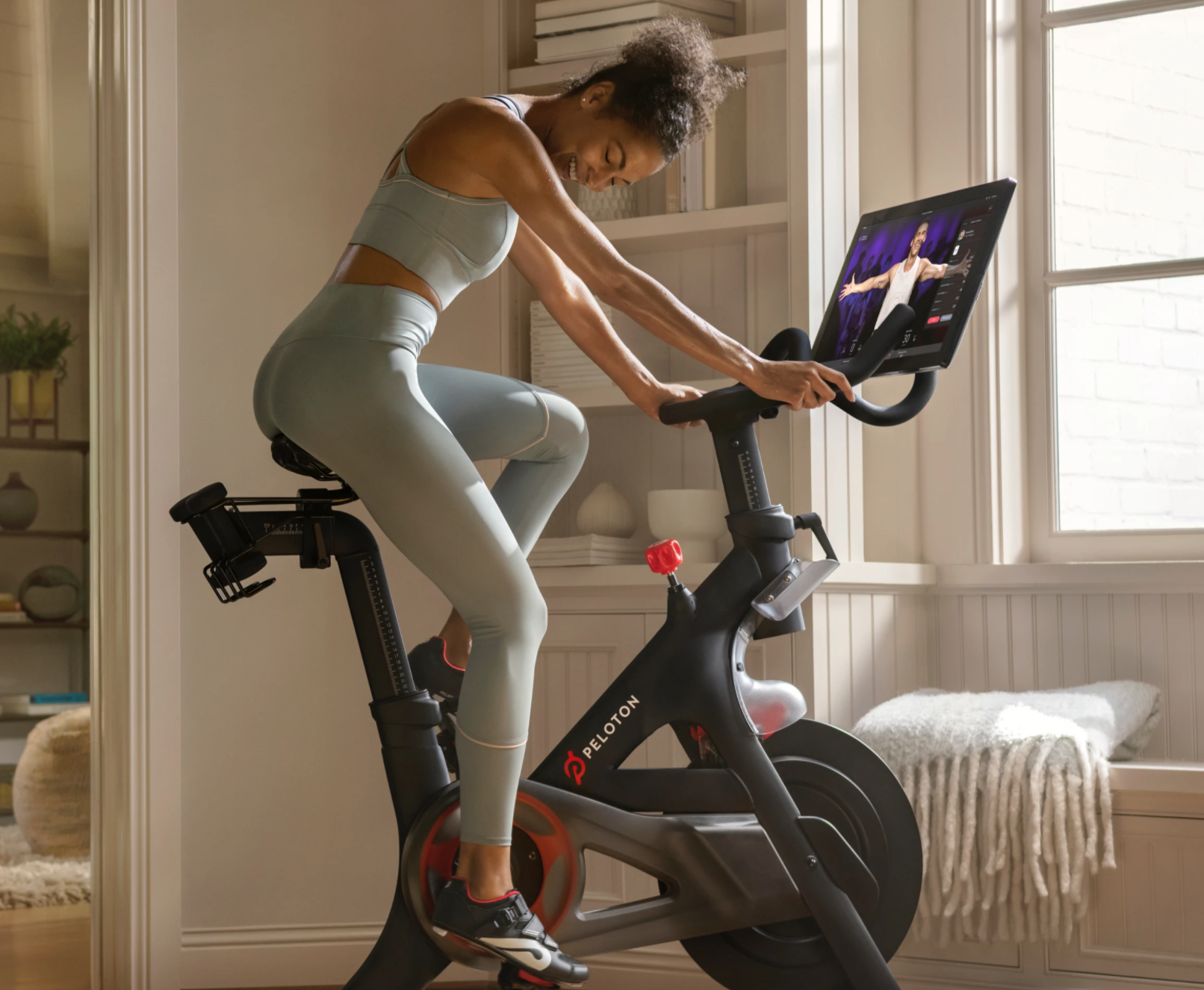 A woman exercises on a Peloton bike in an advertisement for the home fitness brand.