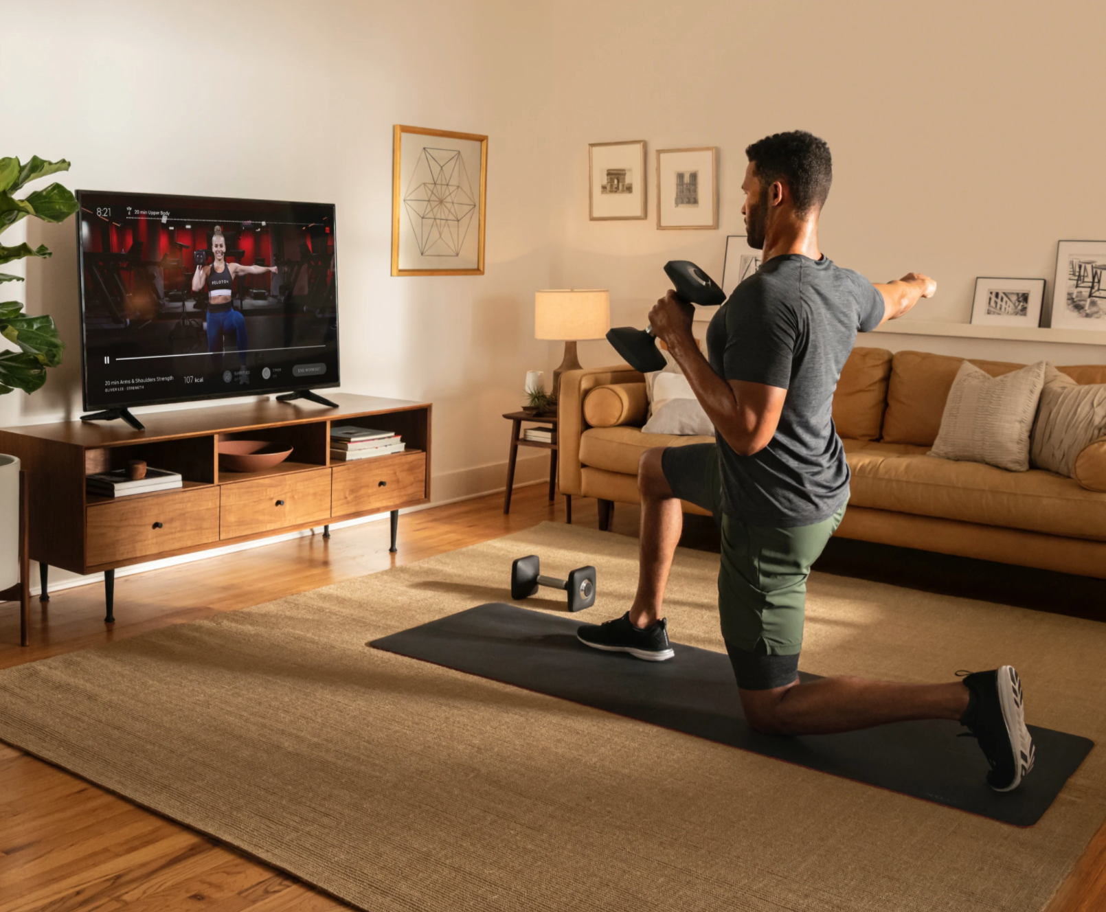 A man exercises at home while following along with a Peloton exercise class on television.