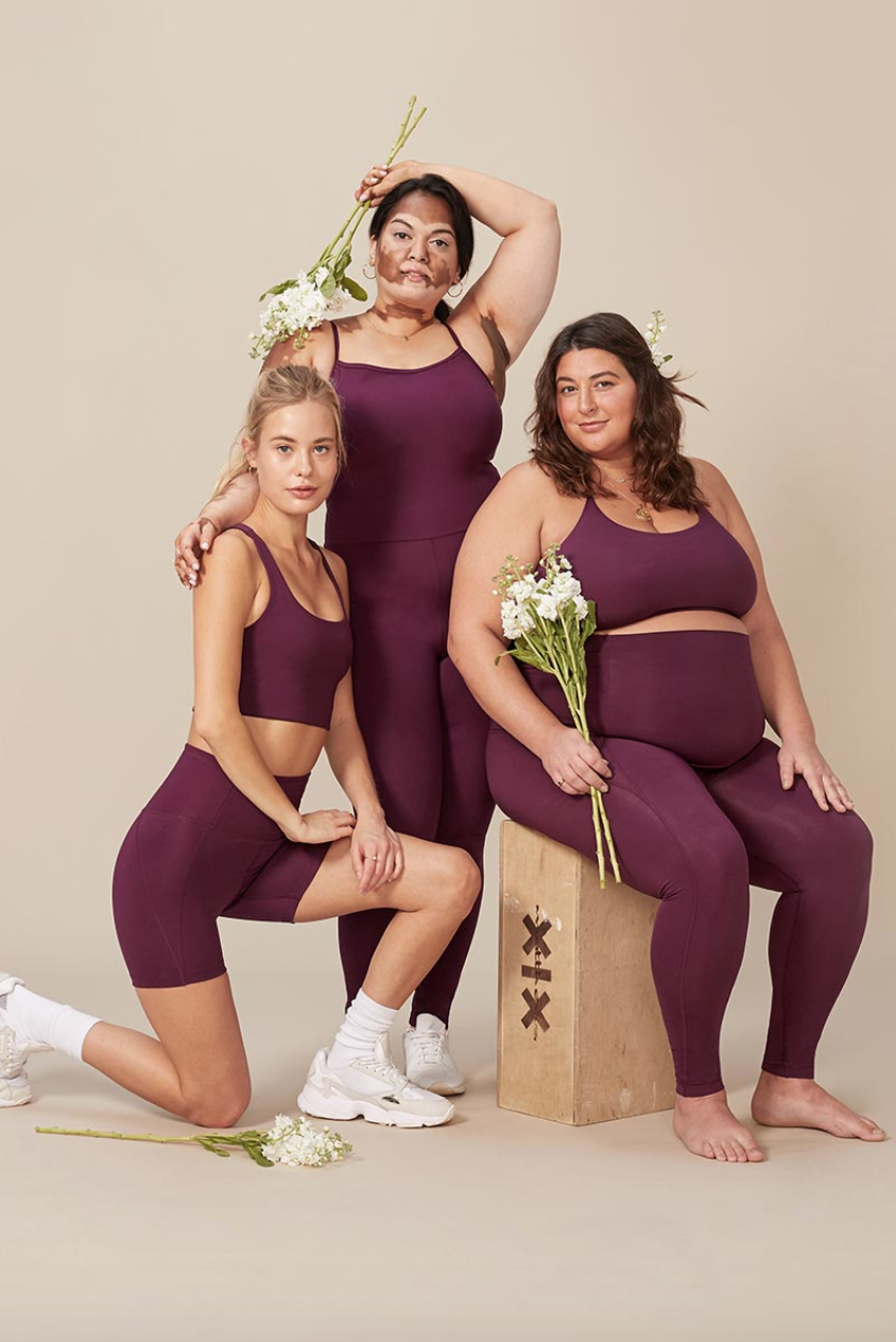 Three models pose wearing athleisure in an advertisement for Girlfriend Collective.