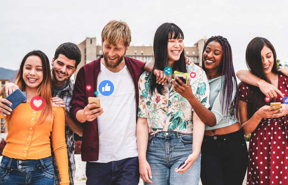A photograph of a group of smiling people looking at and showing each other their phones.