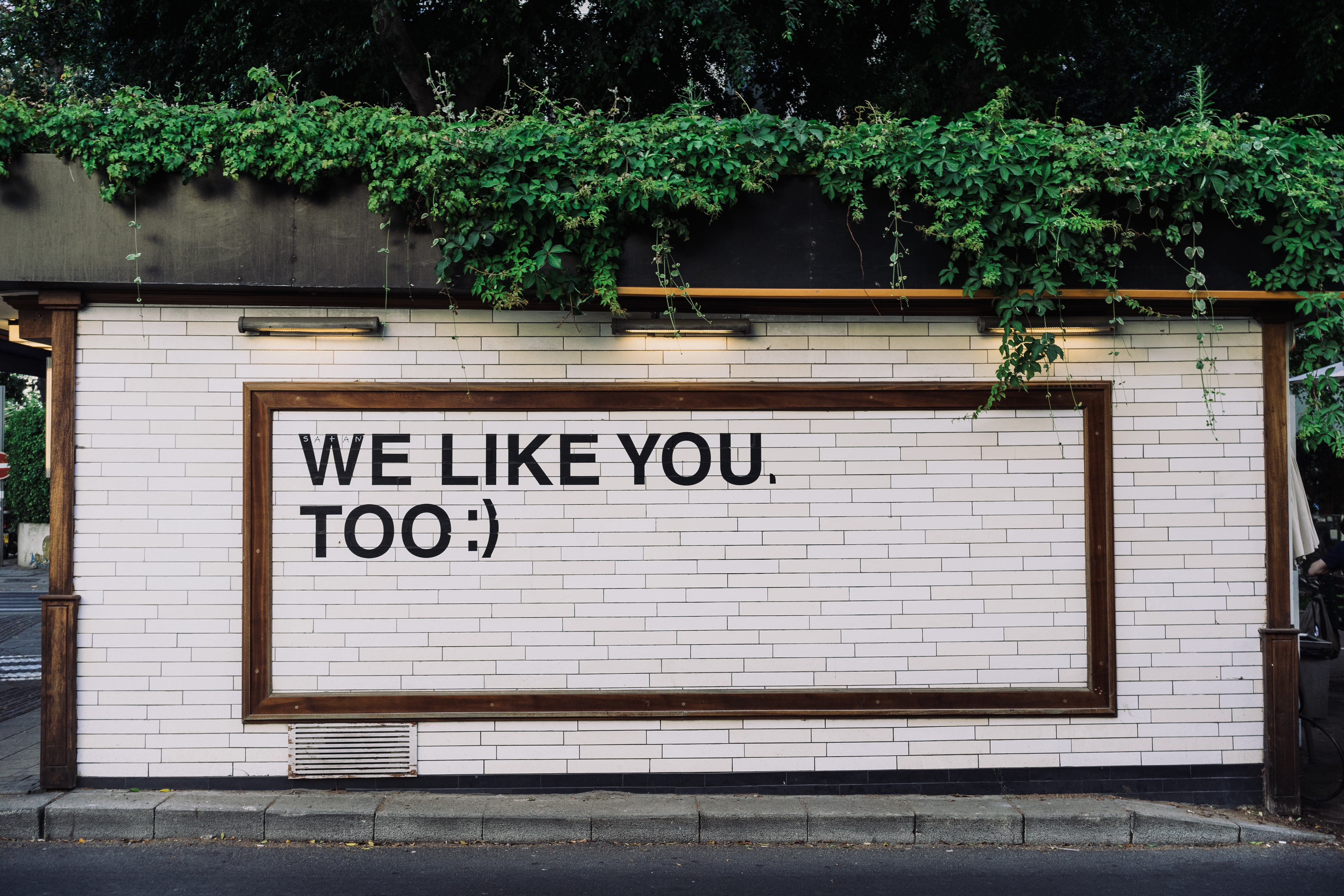 """A photo of a white brick wall with the phrase """"We Like You, Too :)"""" printed on it."""