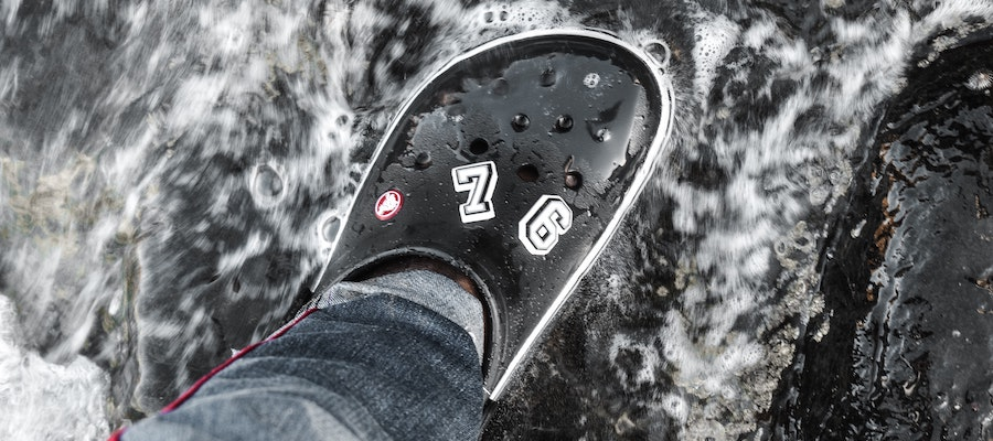A close-up photo of a black Crocs sandal with jibbitz, by Blessing Shock.