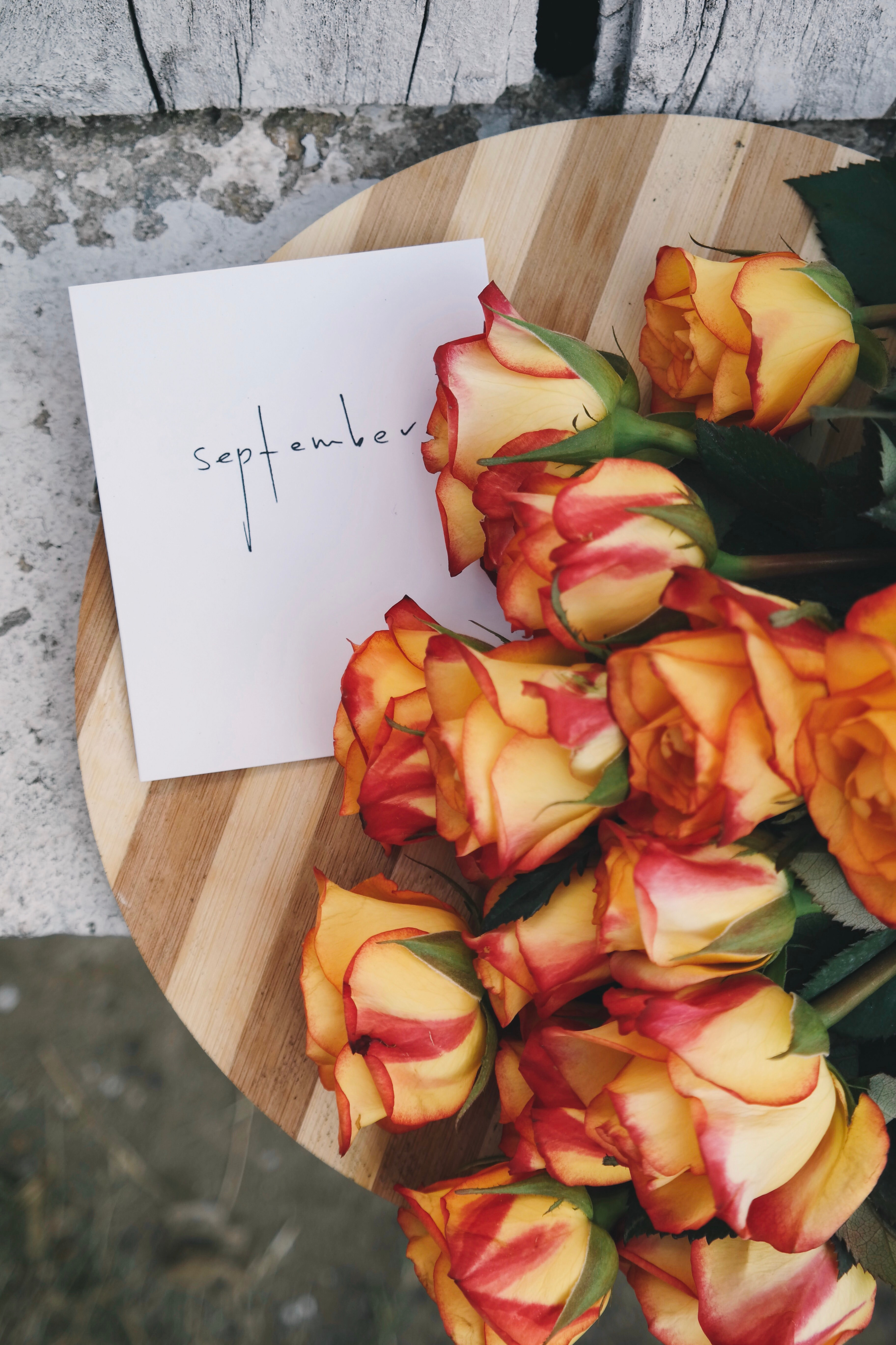 """A flat-lay photo of peach-colored roses and a card with """"September"""" handwritten on the envelope."""