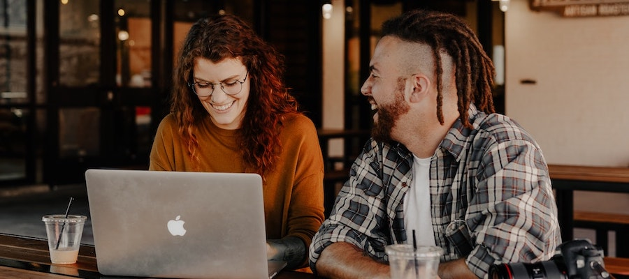 Two influencer marketing professionals working on a laptop, by Brook Cagle.