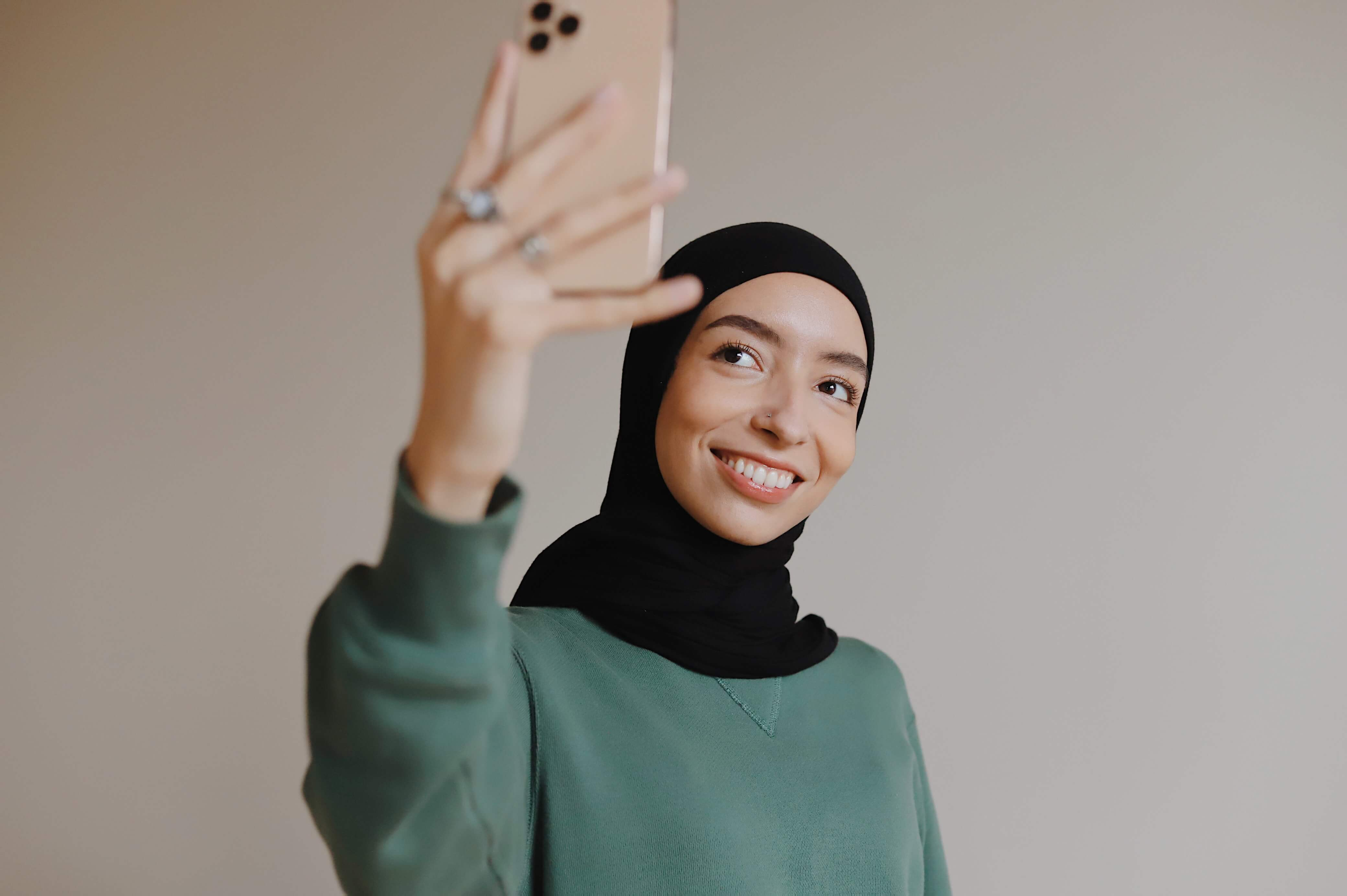 An influencer wearing a hijab takes a selfie.