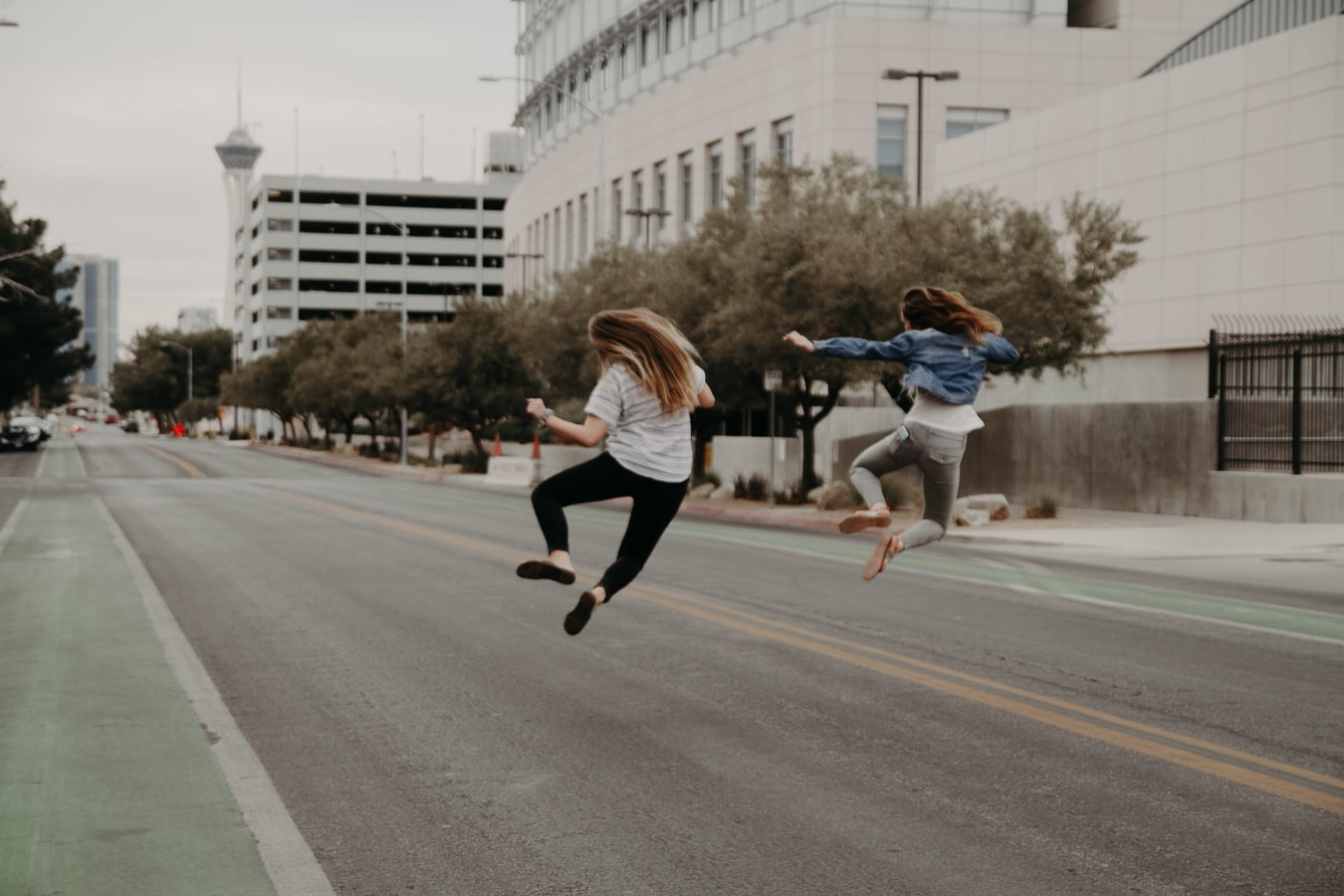 Two influencers jumping side by side in a city street.
