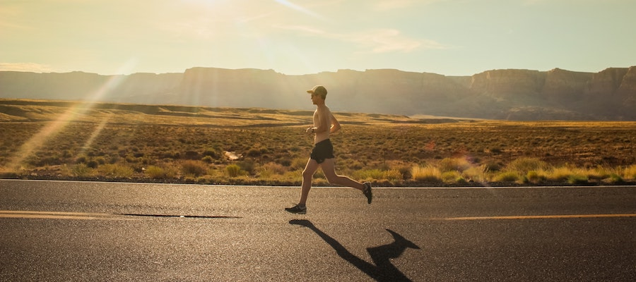 A man running on a road with mountains behind him, by Isaac Wendland.