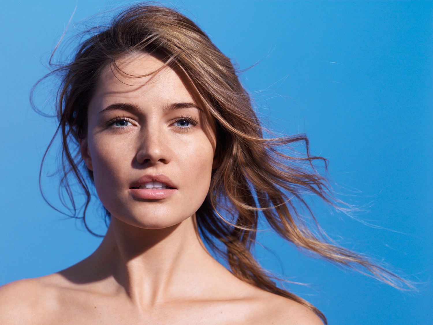 An advertisement for La Roche-Posay featuring a female model against a blue background.