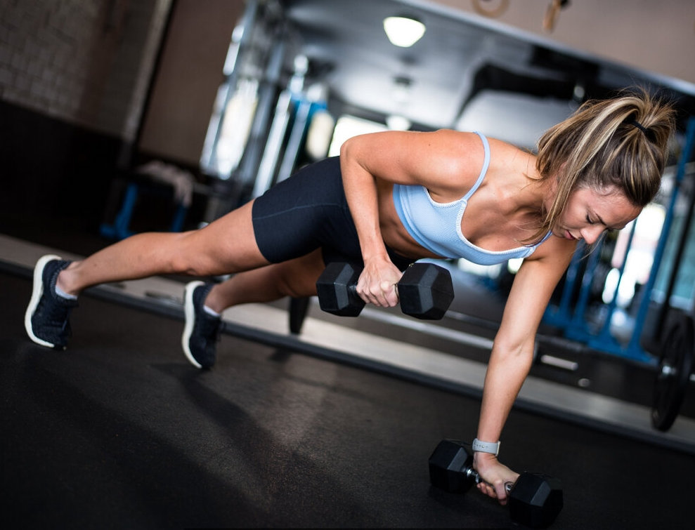 Madeline Custer (@madelinemoves) lifts weights in a plank.