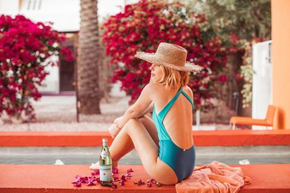 A woman sits by a pool in a Summersalt swimsuit.